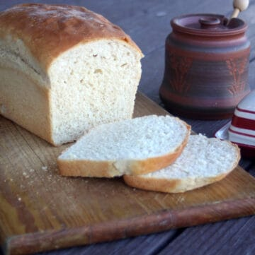 A loaf and slices of peanut butter bread on a board sitting next to a pot of honey and butter dish.