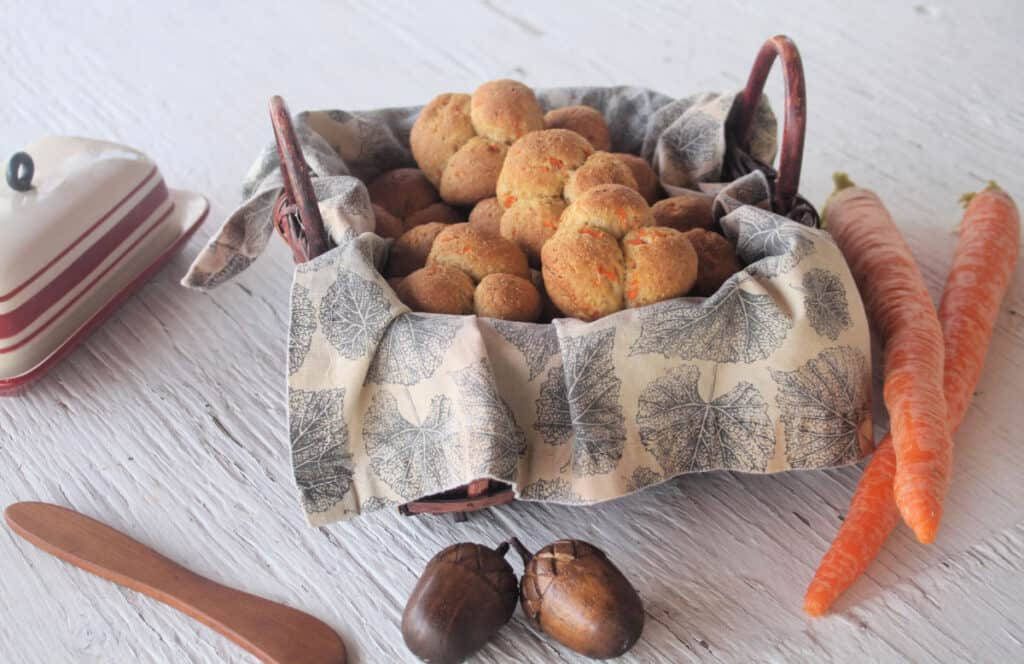 A basket of carrot cloverleaf rolls surrounded by a butter dish and fresh carrots.