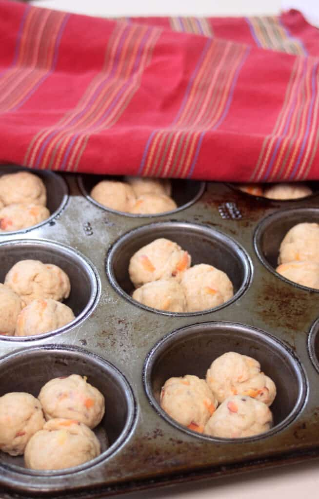 Balls of carrot cloverleaf roll dough inside muffin tin cups ready to rise.