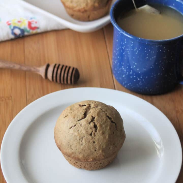 Chai muffin on a white plate surrounded by a blue cup of tea and honey dipper.