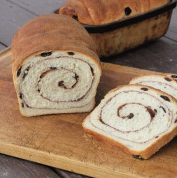A loaf and slices of cinnamon raisin swirl bread on a wooden cutting board.