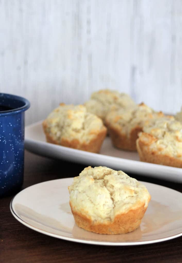 A coconut muffin on a white plate sitting next to a blue coffee cup and in front of a platter of muffins.