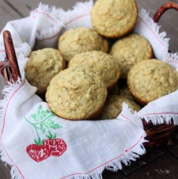Hemp heart oat muffins piled inside a linen lined basket on table.