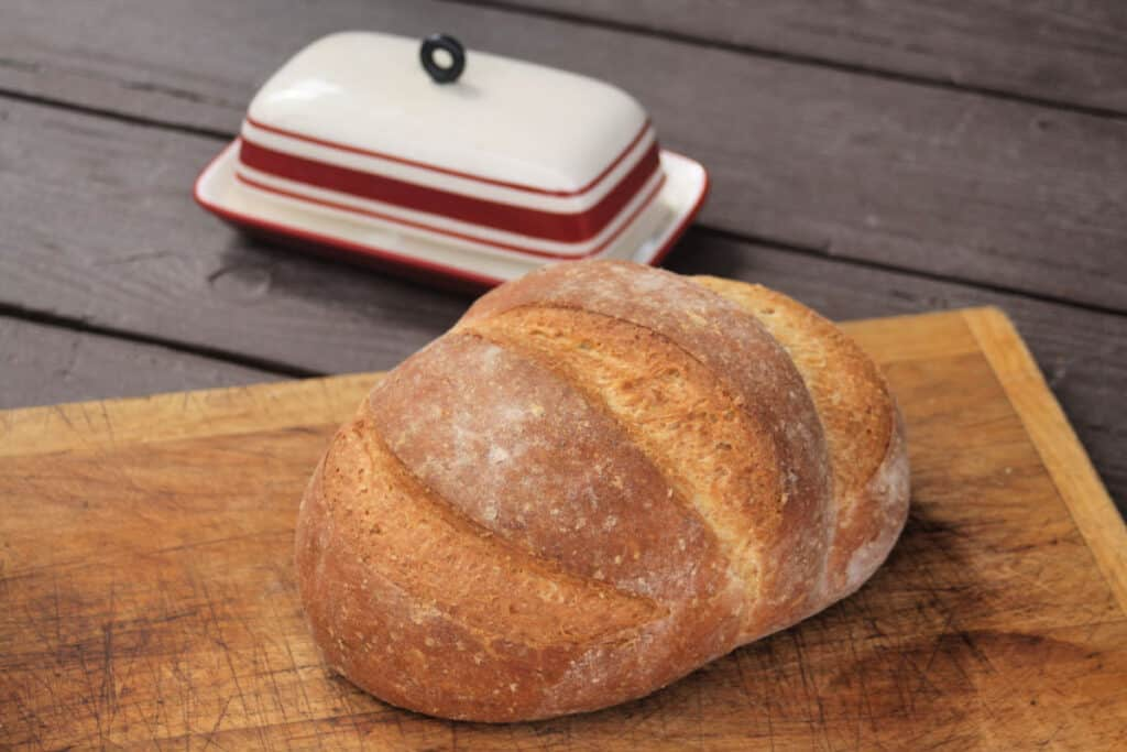 A loaf of honey wheat bran bread on a cutting board with butter dish sitting behind it.