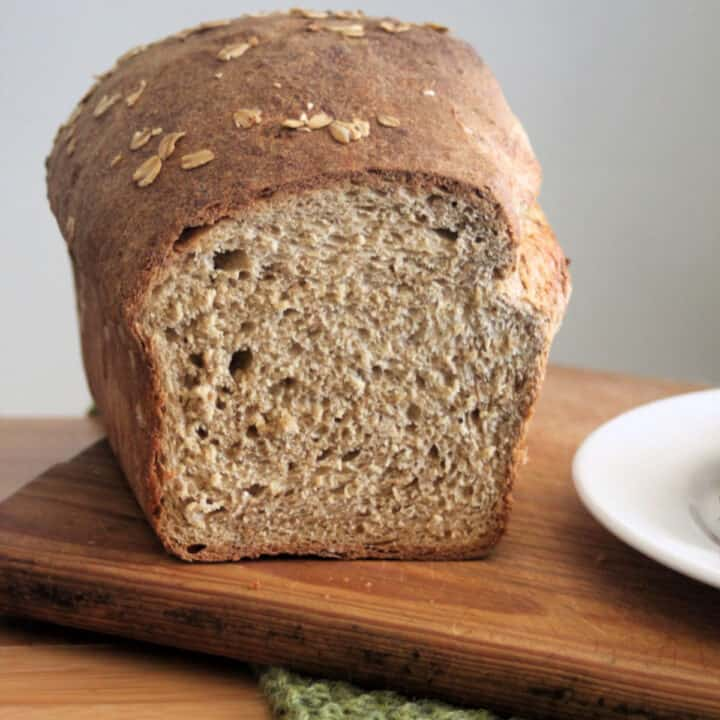 A loaf of oatmeal bread that has end sliced off.