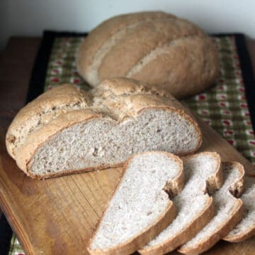 Rye bread slices on a cutting board sitting in front of 2 loaves.