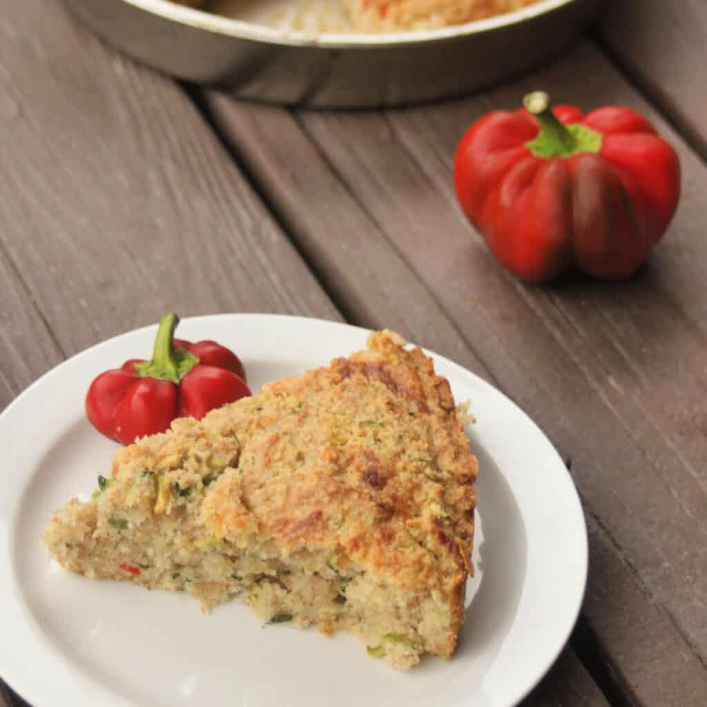 A slice of zucchini cornbread on a white plate surrounded by fresh hot red peppers.