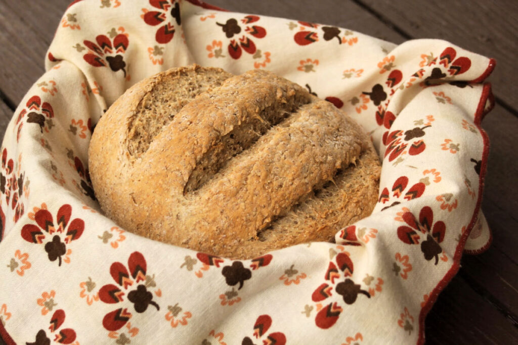 A round loaf of bread in a linen lined basket.