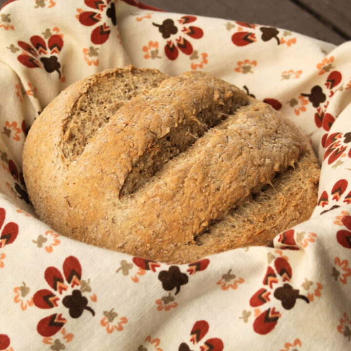 A round loaf of bread sitting inside a linen lined basket.
