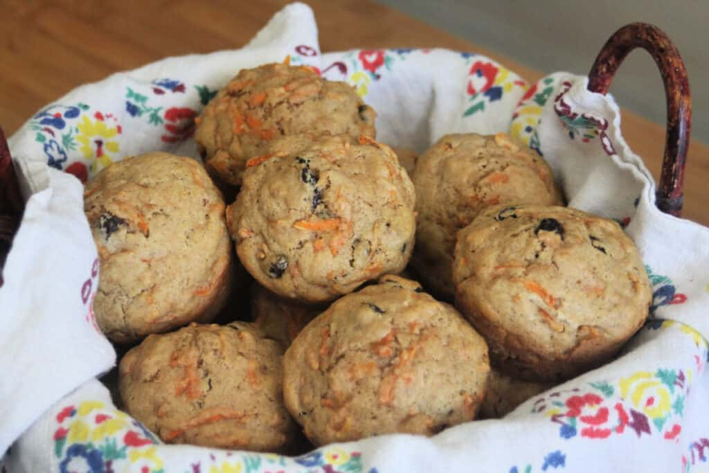 Carrot muffins stacked inside a floral napkin lined basket.