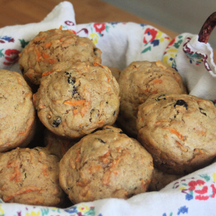 carrot raisin muffins stacked in a napkin lined basket.