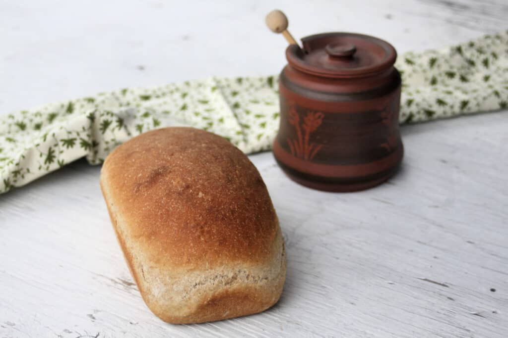 A loaf of honey graham bread on a white board with a clay pot and green and white towel.