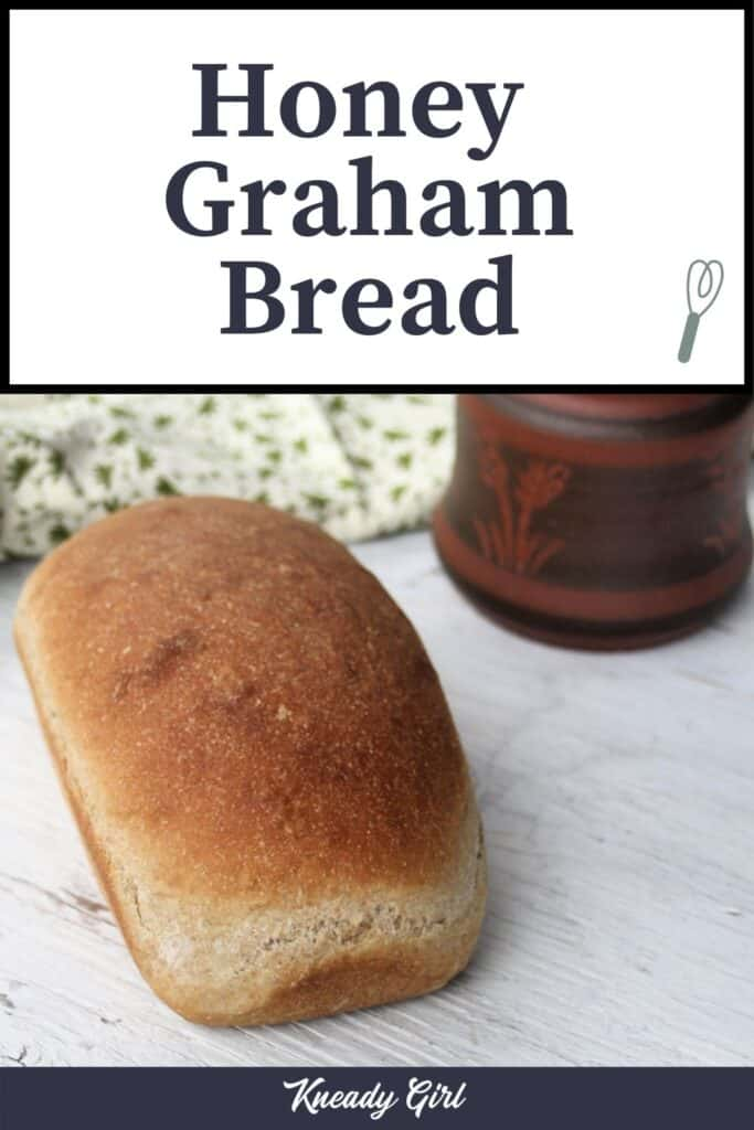 A loaf of honey graham bread on a white table with a towel and clay pot in the background with text overlay.