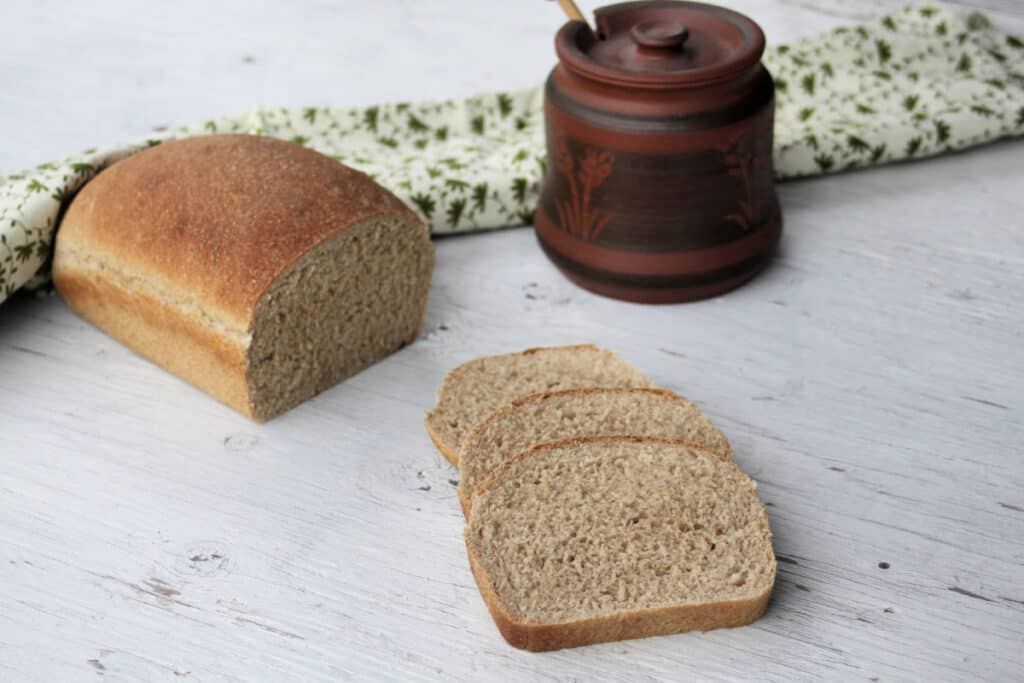 Slices of honey graham bread sitting next to a loaf with a jar of honey and green and white towel.