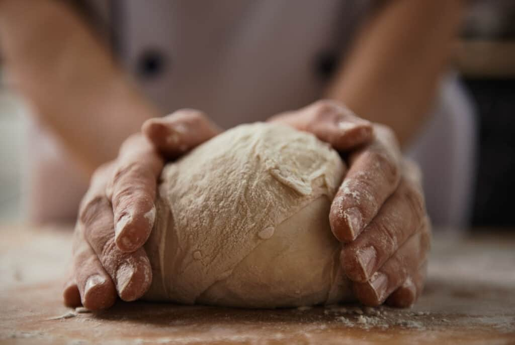 Hands kneading bread dough on a floured board.