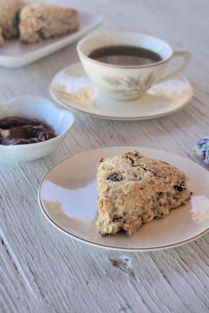 A maple muesli scone on a white plate with a cup of tea, a bowl of jam, and a cloth napkin.