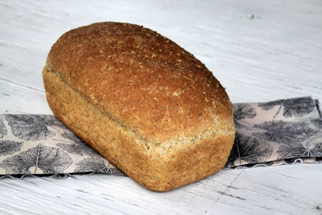 A loaf of mulitgrain bread sitting on napkin on a white table.