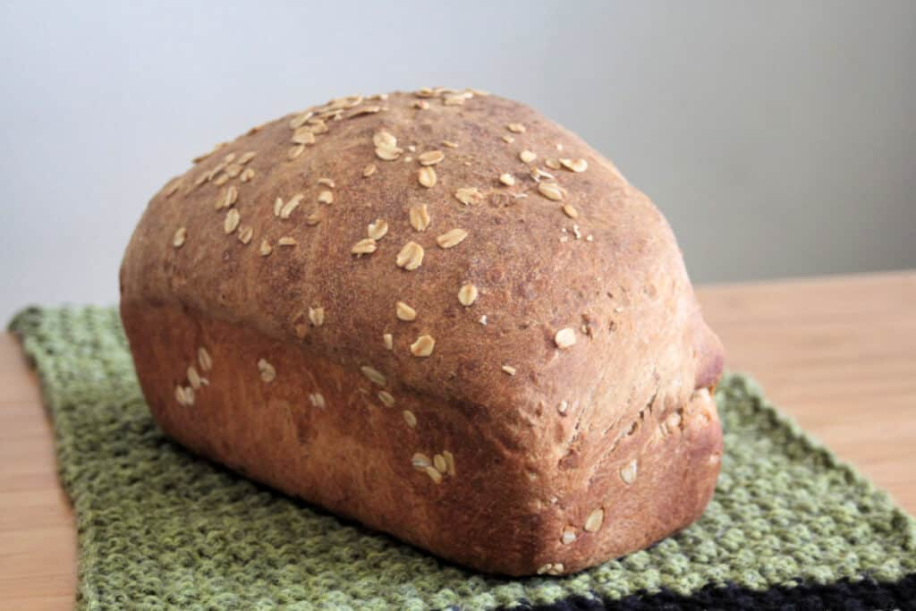 Loaf of oatmeal bread sitting on green knitted table runner.