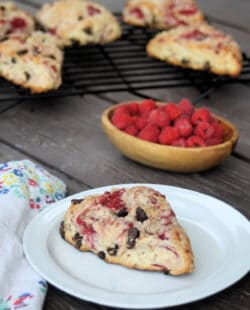 A raspberry scone on a white plate sitting next to a napkin. In the background is a bowl of fresh raspberries and more scones on a wire rack.
