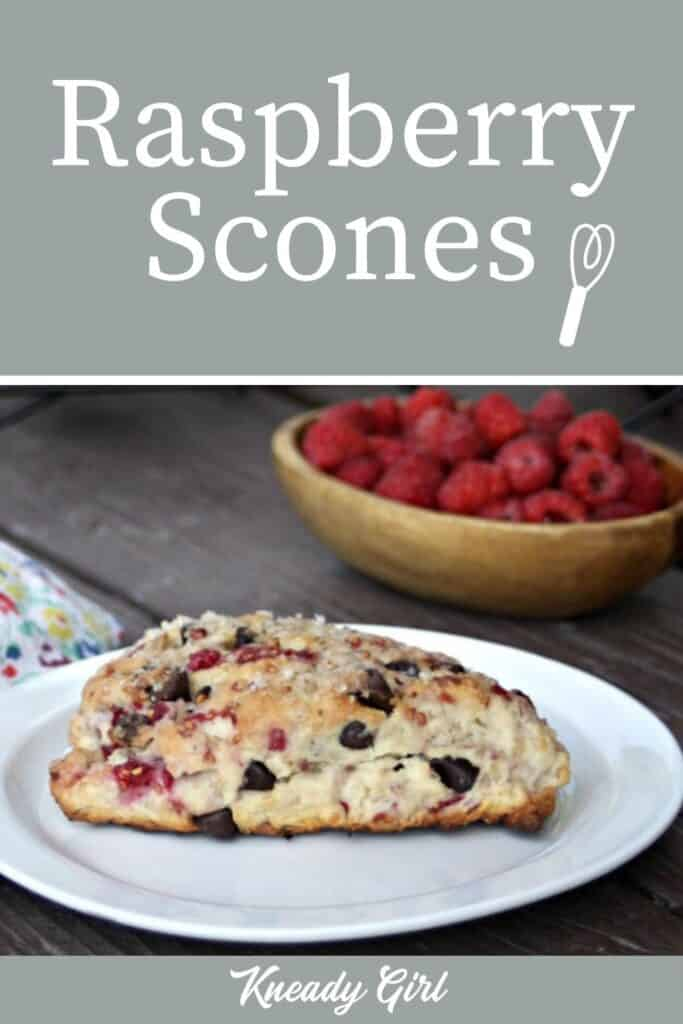 A raspberry chocolate chip scone on a white plate sitting in front of a bowl of berries with text overlay.