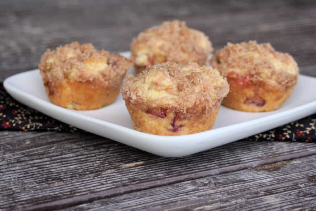 4 rhubarb muffins sitting on a square white plate.