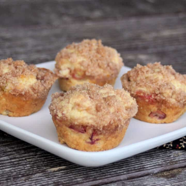 4 rhubarb muffins on a square, white plate.
