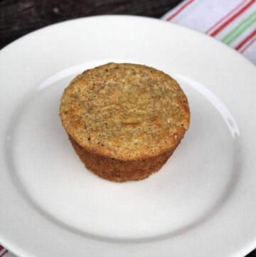 A single yogurt bran muffin sitting on a white plate on top of a red and white striped towel.