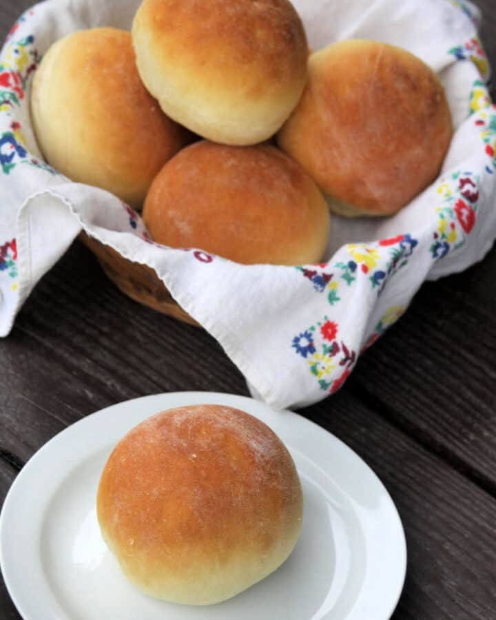 A yogurt dinner roll sitting on a white plate in front of a basket full of more rolls.