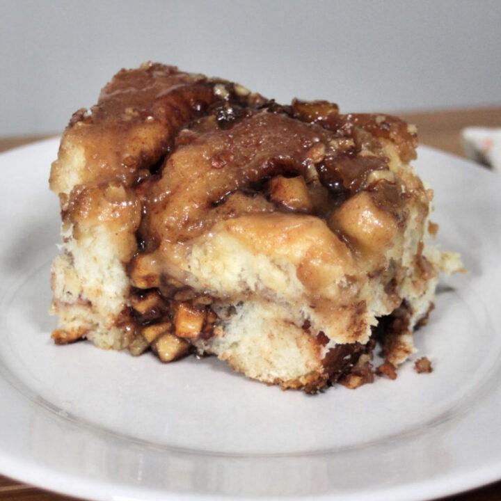 A caramel apple cinnamon roll on a white plate.