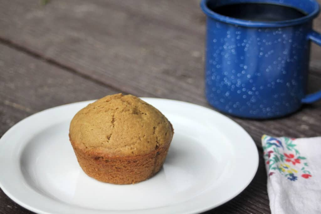 A coffee muffin on a white plate with a floral napkin and blue tin cup full of coffee next to it on the table.