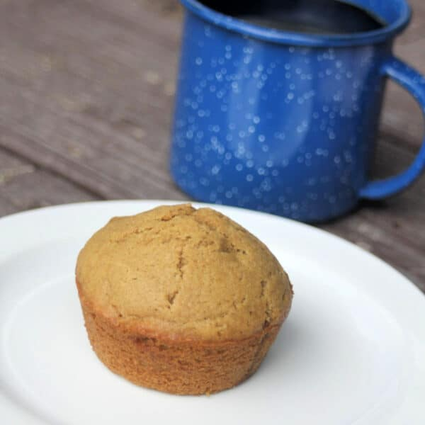 A coffee muffin on a white plate with a blue tin cup of coffee sitting behind it.