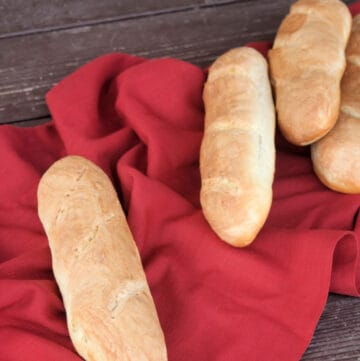 Loaves of french bread scattered on a red cloth.