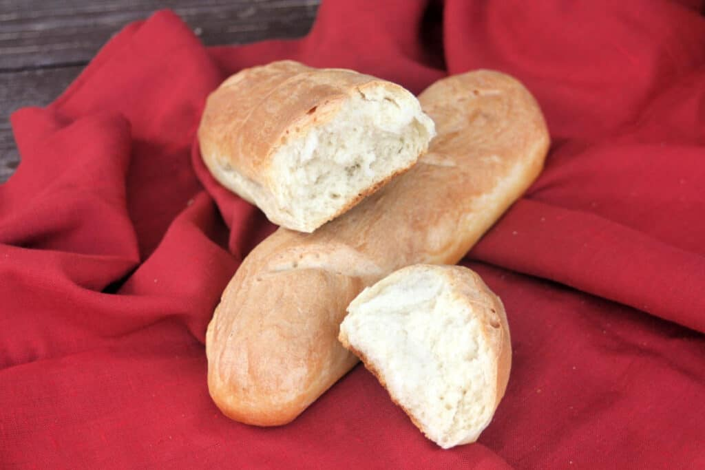 Pieces of french bread sitting on top of a whole loaf on a red cloth
