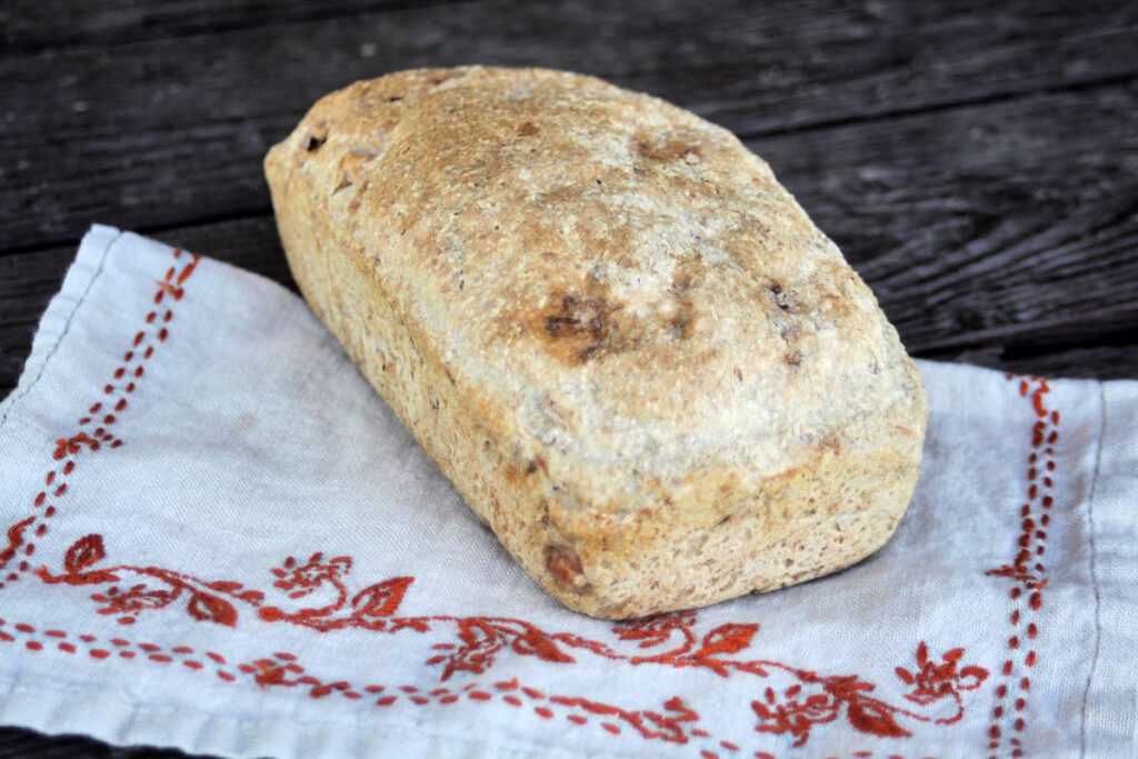 A loaf of ham bread sitting on an embroidered napkin.
