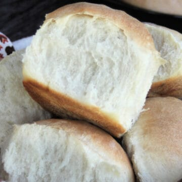 A close up of a yeast roll sitting on top of a basket of rolls lined with a napkin.