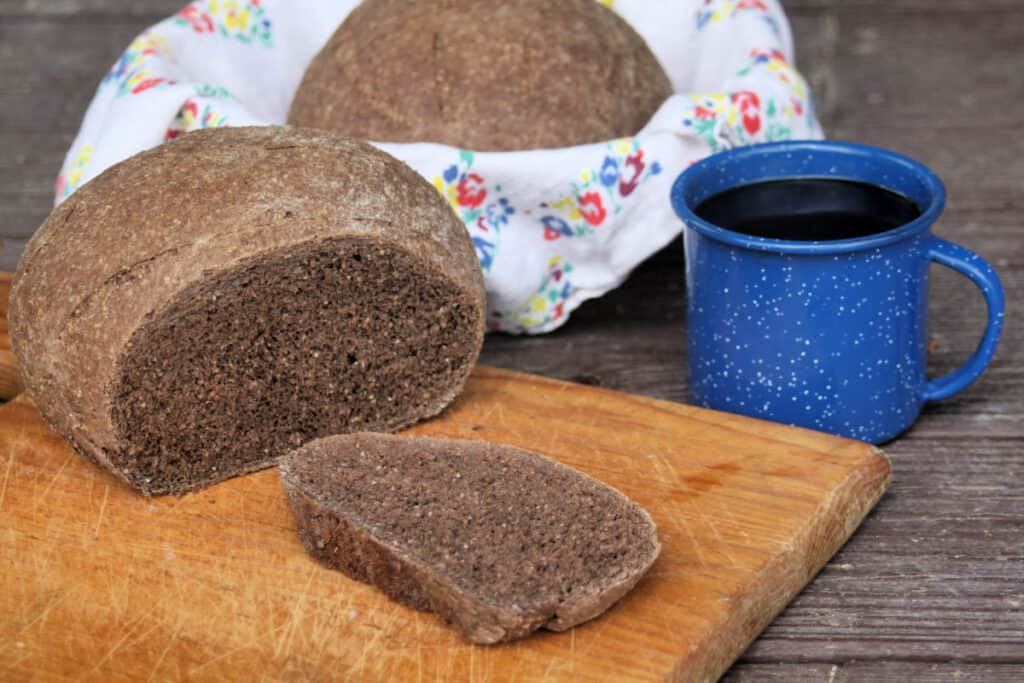 A slice of honey wheat brown bread on a wooden cutting board next to the loaf sitting with a cup of coffee on a table and another loaf sitting in a floral napkin lined basket.