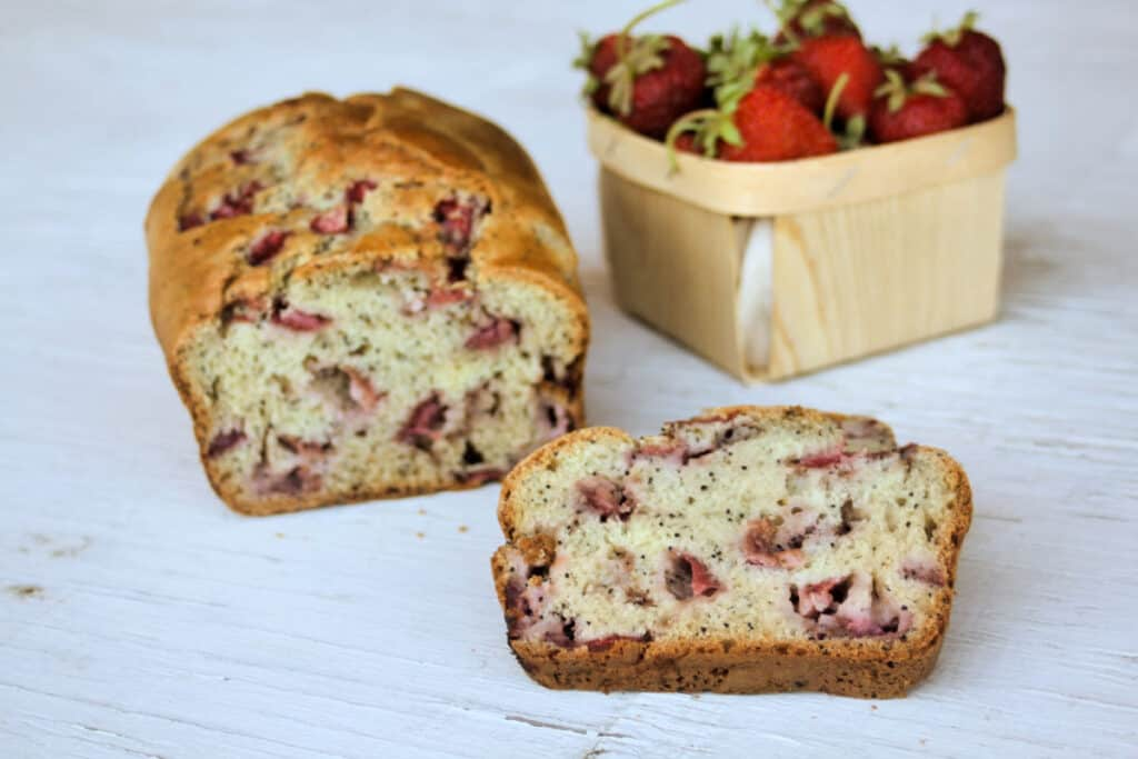 slices of strawberry bread sitting in front of the loaf and a basket of fresh strawberries.