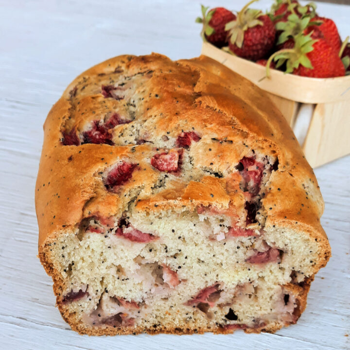 Strawberry quick bread on a white board with a basket of fresh strawberries behind it.