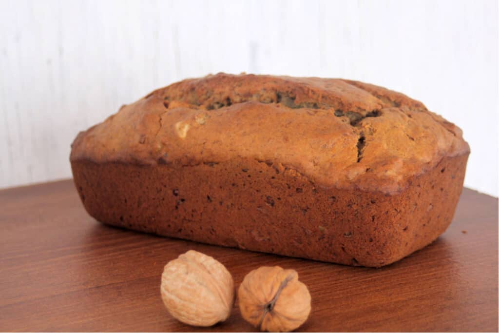 a loaf of banana bread on a table with walnuts still in shell.