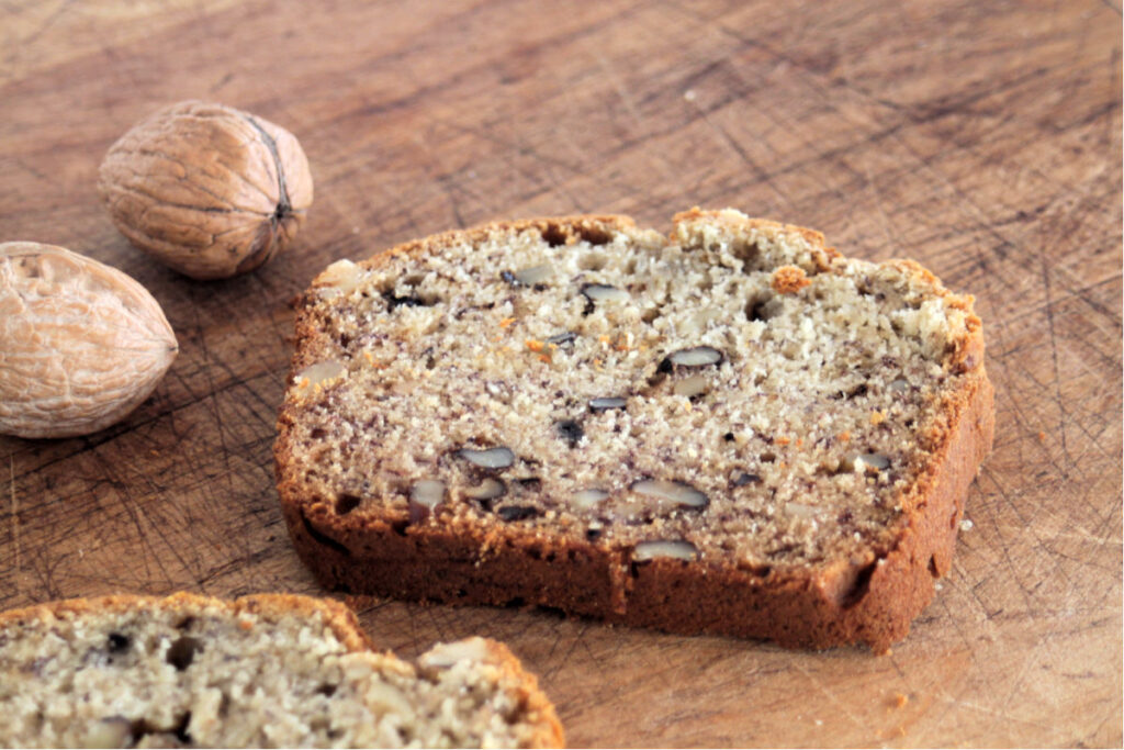 A slice of buttermilk banana bread on a cutting board with whole walnuts in their shell.