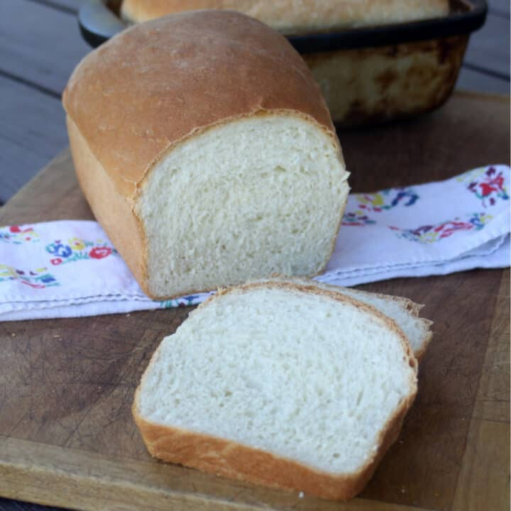 Slices of buttermilk bread sitting on a board with rest of loaf and floral napkin.