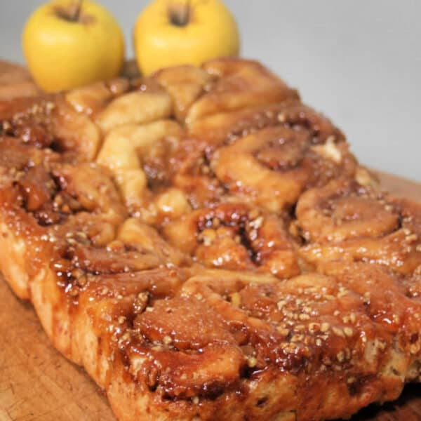 Caramel apple cinnamon rolls sitting on a wooden board with fresh apples behind it.