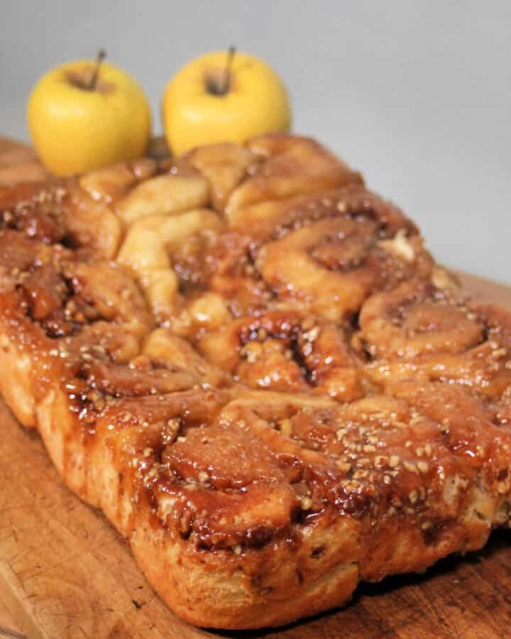 Caramel apple cinnamon rolls sitting on a wooden board with fresh apples behind it.