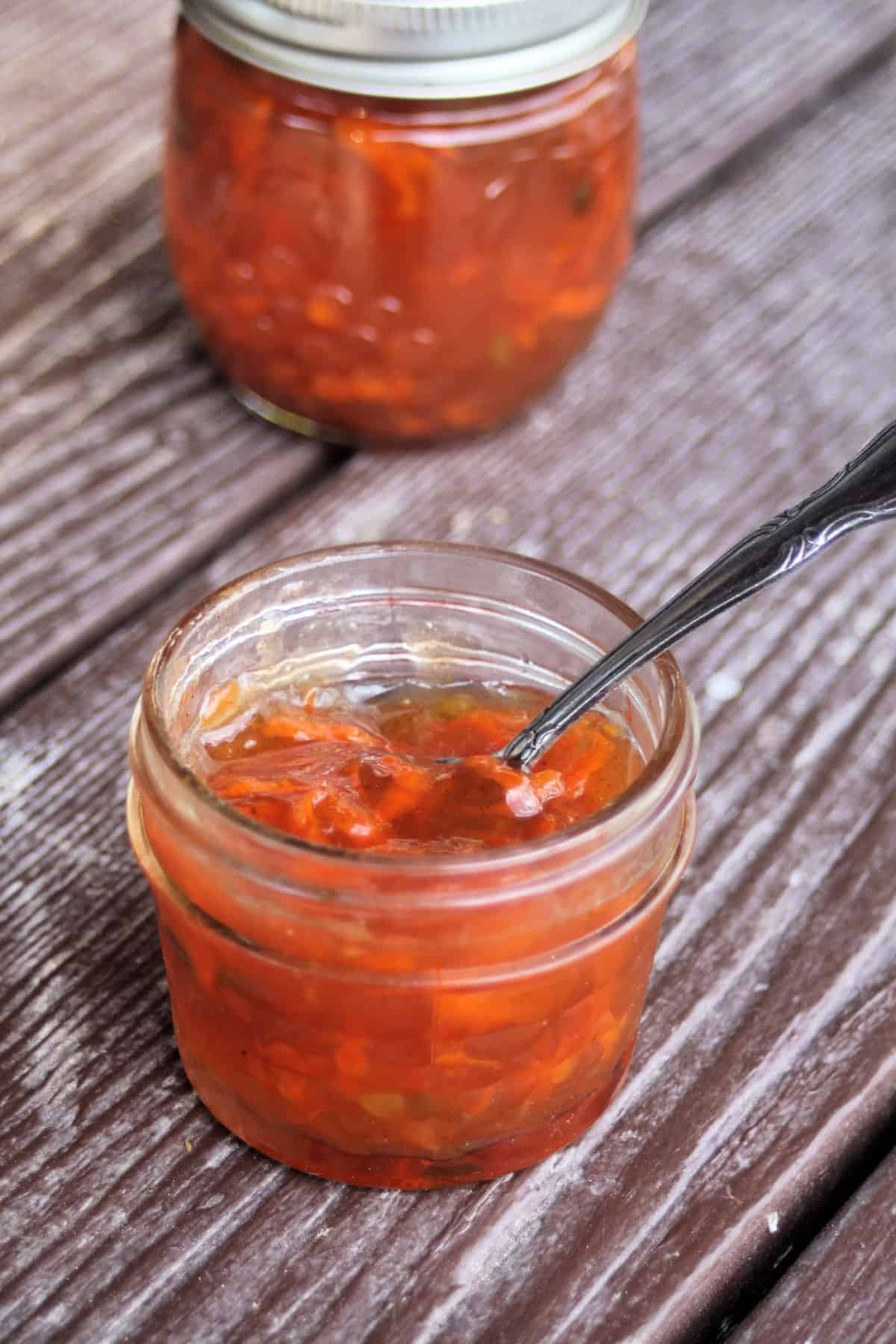 Carrot jam in an open a jar with a spoon inside it, sitting in front of a sealed jar.
