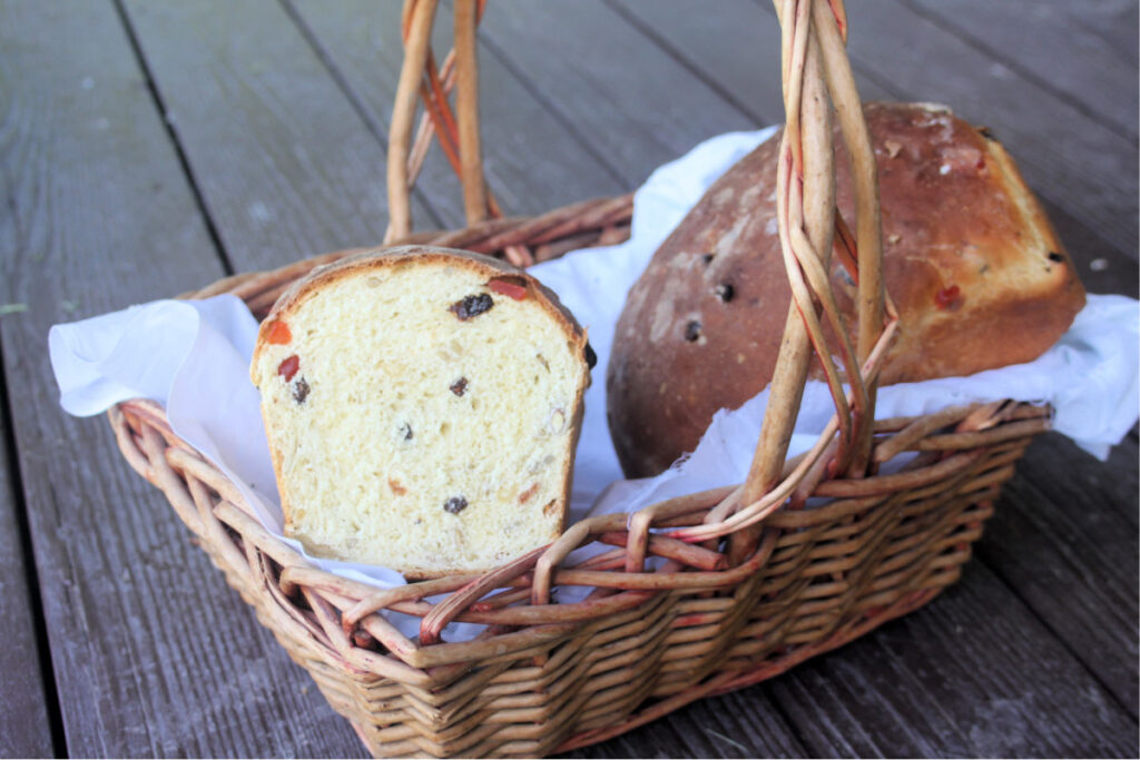 2 loaves of harvest bread in a white linen lined basket, 1 loaf has the end cut off exposing the insides.