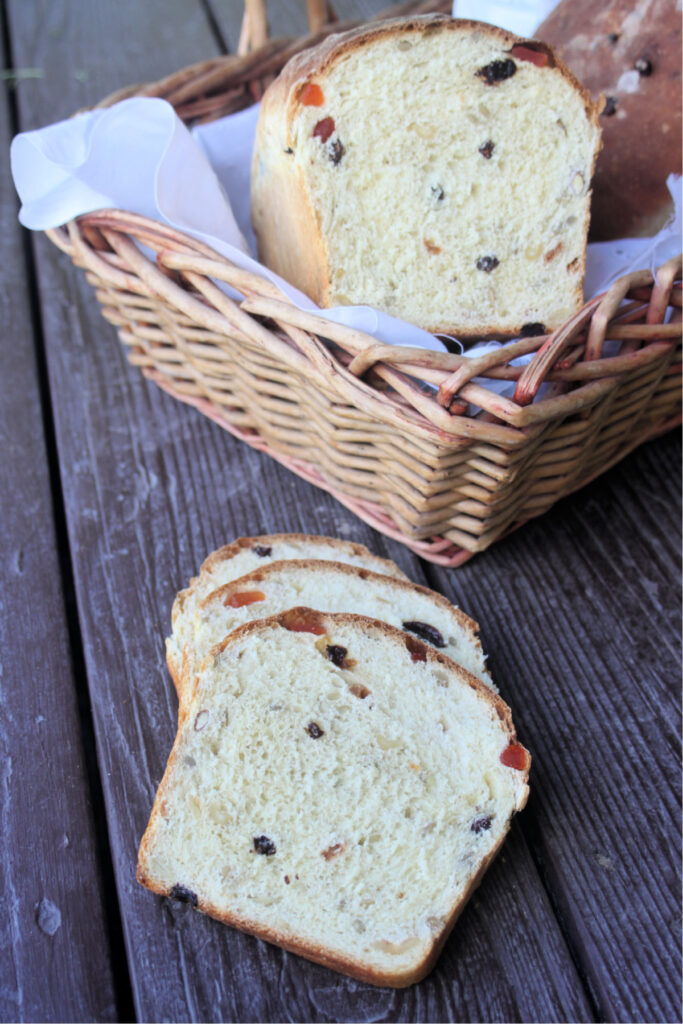 slices of harvest bread on a dark board sitting in front of a basket containing the rest of the loaf and another whole loaf of bread.