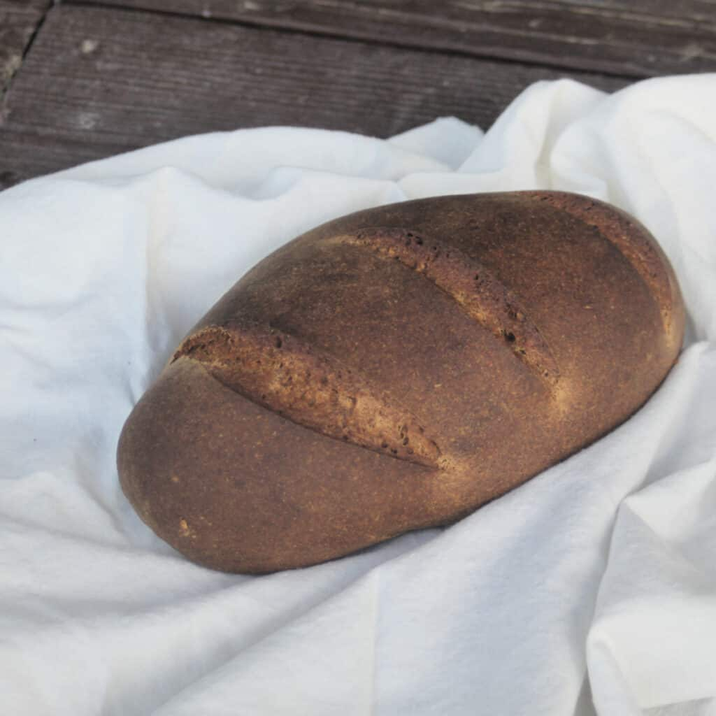 A loaf of pumpernickel bread on a white cloth.