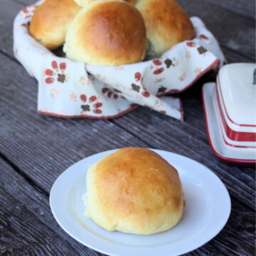 A sweet potato bun on a white plate sitting in front of a basket full of more buns and a butter dish.