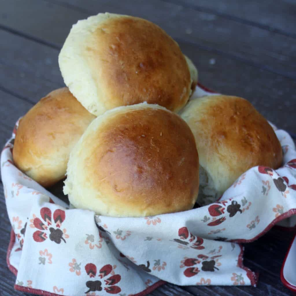 a napkin lined basket overflowing with sweet potato buns.
