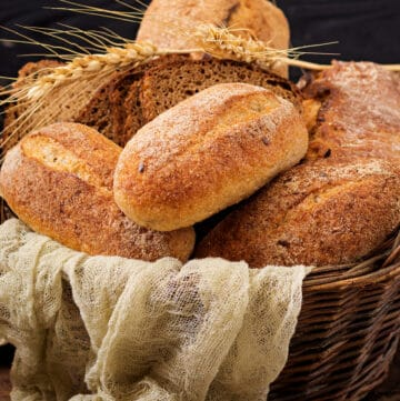 A basket full of different kinds of breads with a napkin hanging over the edge.